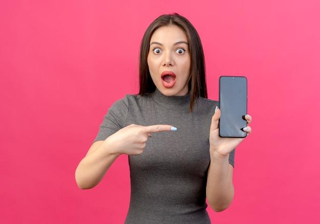 Onder de indruk jonge mooie vrouw die en op mobiele telefoon houdt richt die op roze achtergrond wordt geïsoleerd