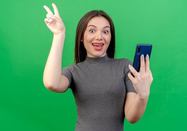 Onder de indruk jonge mooie vrouw die mobiel houdt en de telefoon van het vredesteken doet die op groene achtergrond wordt geïsoleerd