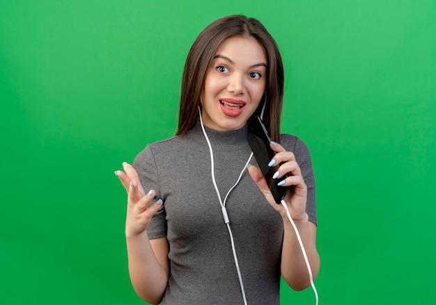 Onder de indruk jonge mooie vrouw die oortelefoons draagt die kant houden hand in lucht kijken en op telefoon spreken die op groene achtergrond met exemplaarruimte wordt geïsoleerd