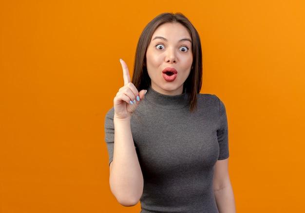 Onder de indruk jonge mooie vrouw die vinger opheft die op oranje achtergrond met exemplaarruimte wordt geïsoleerd