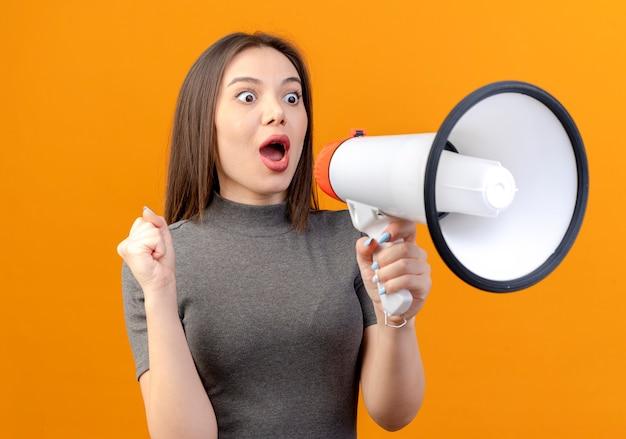 Onder de indruk jonge mooie vrouw gebalde vuist op zoek rechtdoor en pratend door de spreker