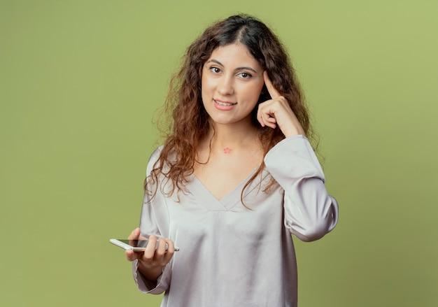 Onder de indruk jonge mooie vrouwelijke kantoormedewerker die telefoon houdt en vinger op het hoofd zet dat op olijfgroene muur wordt geïsoleerd