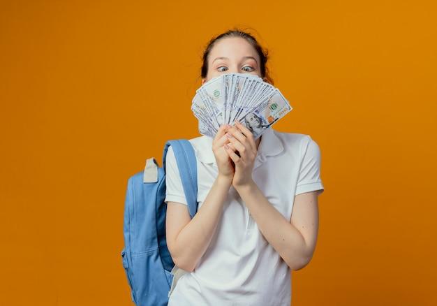 Onder de indruk jonge mooie vrouwelijke student die achterzak draagt ?? die en geld bekijkt dat op oranje achtergrond met exemplaarruimte wordt geïsoleerd
