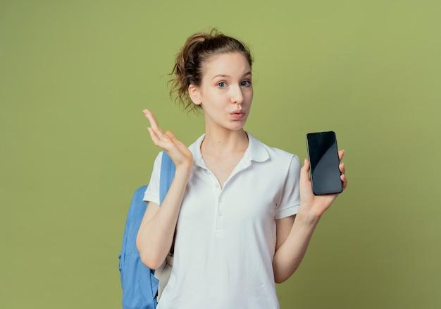 Onder de indruk jonge mooie vrouwelijke student die achterzak draagt die mobiele telefoon toont en hand in lucht houdt die op groene achtergrond met exemplaarruimte wordt geïsoleerd
