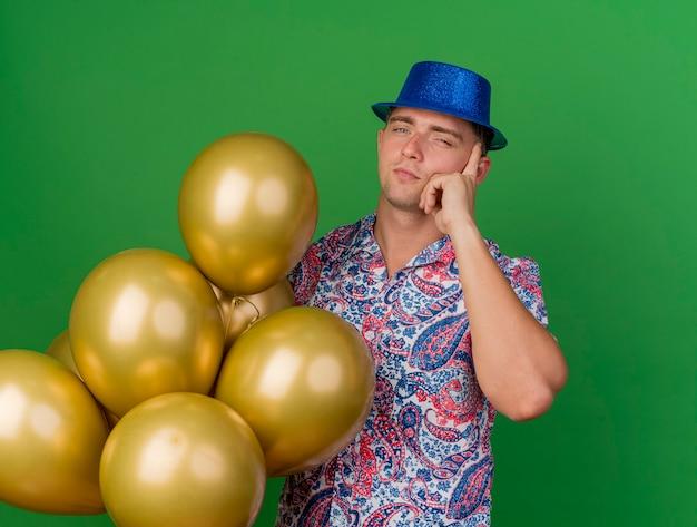 Onder de indruk jonge partij kerel die blauwe hoed draagt die ballons houdt en hand op tempel zet die op groen wordt geïsoleerd