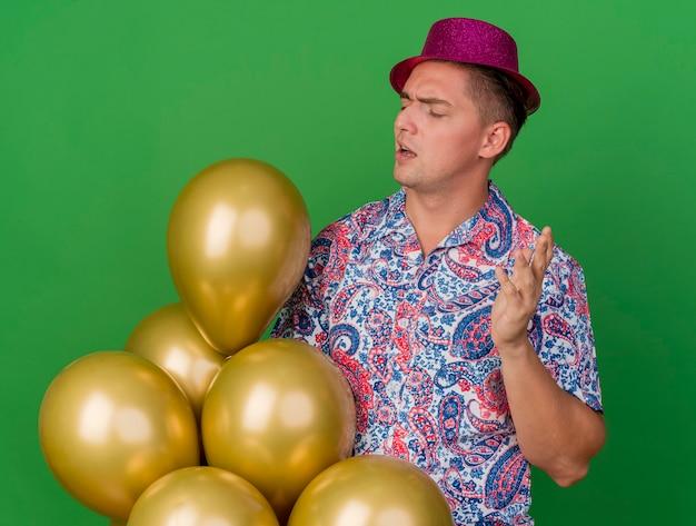 Onder de indruk jonge partij kerel die roze hoed draagt ?? die en ballons bekijkt die op groen worden geïsoleerd