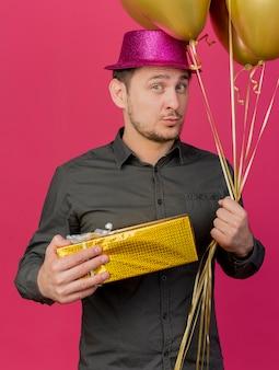 Onder de indruk jonge partij kerel die roze hoed draagt die giftdoos met ballons draagt die op roze achtergrond wordt geïsoleerd