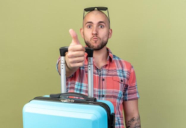 Onder de indruk jonge reiziger man met zonnebril met koffer en duimen omhoog geïsoleerd op olijfgroene muur met kopieerruimte