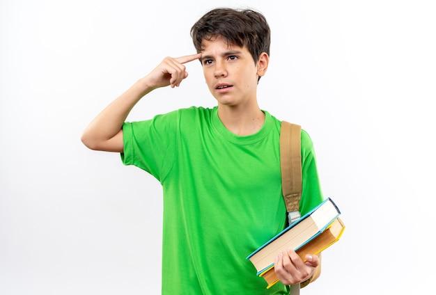 Onder de indruk jonge schooljongen met rugzak met boeken die de vinger op de tempel zetten die op een witte muur is geïsoleerd