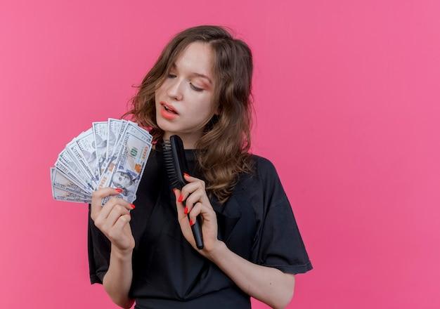 Onder de indruk jonge slavische vrouwelijke kapper die eenvormige holdingskam en geld draagt ?? die geld bekijkt dat op roze achtergrond met exemplaarruimte wordt geïsoleerd