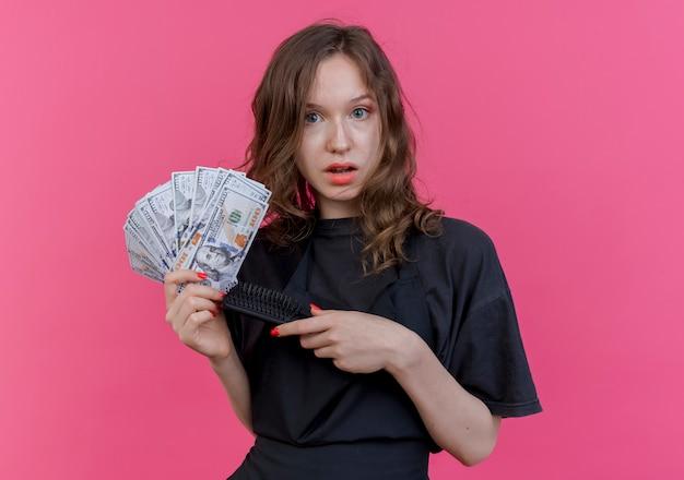 Onder de indruk jonge slavische vrouwelijke kapper die eenvormige holdingskam en geld draagt die op roze achtergrond wordt geïsoleerd