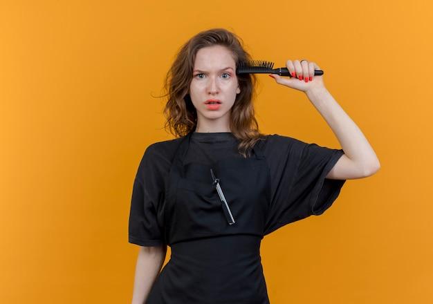 Onder de indruk jonge slavische vrouwelijke kapper dragen uniforme aanwijsapparaat kam aan het hoofd geïsoleerd op een oranje achtergrond met kopie ruimte