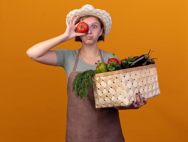 Onder de indruk jonge slavische vrouwelijke tuinman die tuinierende hoed draagt die plantaardige mand en tomaat voor oog op sinaasappel houdt