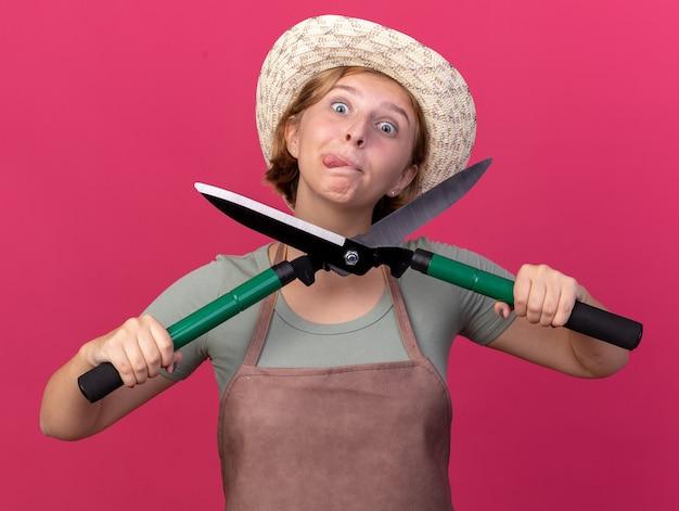 Onder de indruk jonge slavische vrouwelijke tuinman met tuinhoed steekt tong uit en houdt tuinschaar geïsoleerd op roze muur met kopieerruimte