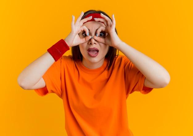 Onder de indruk jonge sportieve vrouw die hoofdband en polsbandjes draagt die blikgebaar doen kijkend gebruikend handen als verrekijker