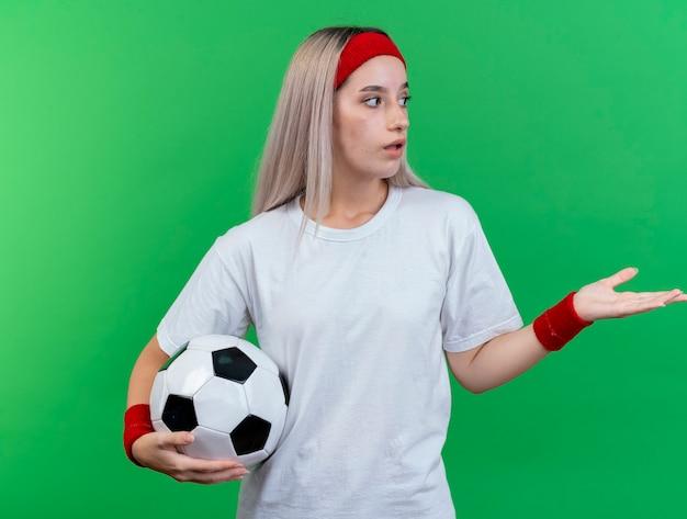 Onder de indruk jonge sportieve vrouw met beugels dragen hoofdband en polsbandjes houdt bal kijken en wijzend naar kant geïsoleerd op groene muur
