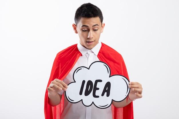 Onder de indruk jonge superheld jongen in rode cape houden en kijken naar idee zeepbel geïsoleerd op een witte achtergrond met kopie ruimte