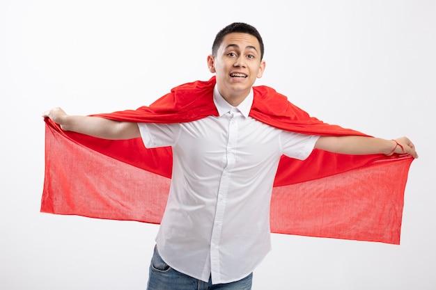 Onder de indruk jonge superheld jongen in rode cape kijken camera strekken handen grijpen cape doen alsof vliegen geïsoleerd op een witte achtergrond