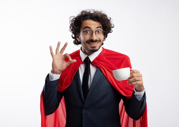 Onder de indruk jonge superheld man in optische bril dragen pak met rode mantel houdt beker en gebaren ok handteken geïsoleerd op een witte muur