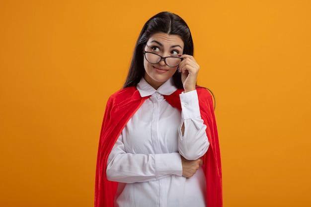Onder de indruk jonge supervrouw die een bril draagt die hen grijpt die naar kant kijkt die op oranje muur wordt geïsoleerd