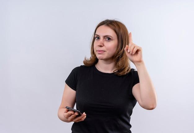 Onder de indruk jonge toevallige vrouw die mobiele telefoon houdt en vinger op geïsoleerde witte ruimte met exemplaarruimte opheft