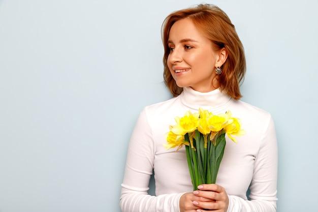 Onder de indruk jonge vrouw die mooi boeket van narcissen bloemen houdt, glimlachend, emotioneel en verrast, opzij kijkend naar kopie ruimte. blauw oppervlak. zomertijd. geniet van de kleine dingen