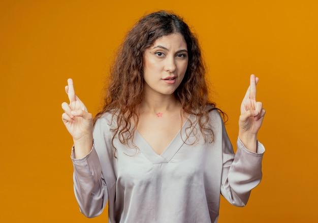 Onder de indruk jonge vrouw kruising vingers geïsoleerd op geel