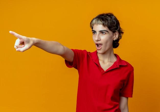 Onder de indruk jonge vrouw met pixiekapsel die naar kant kijkt en wijst