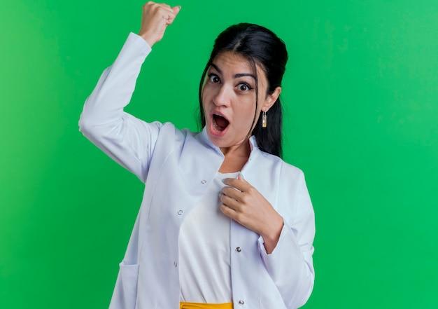 Onder de indruk jonge vrouwelijke arts die medisch kleed draagt dat hand op borst houdt en vuist opheft die op groene muur met exemplaarruimte wordt geïsoleerd