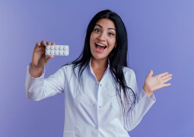 Onder de indruk jonge vrouwelijke arts die medische mantel draagt die een pak medische tabletten toont, die met lege hand kijkt
