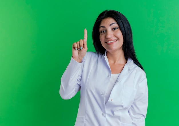 Onder de indruk jonge vrouwelijke arts die medische mantel draagt die glimlachend en vinger opheft