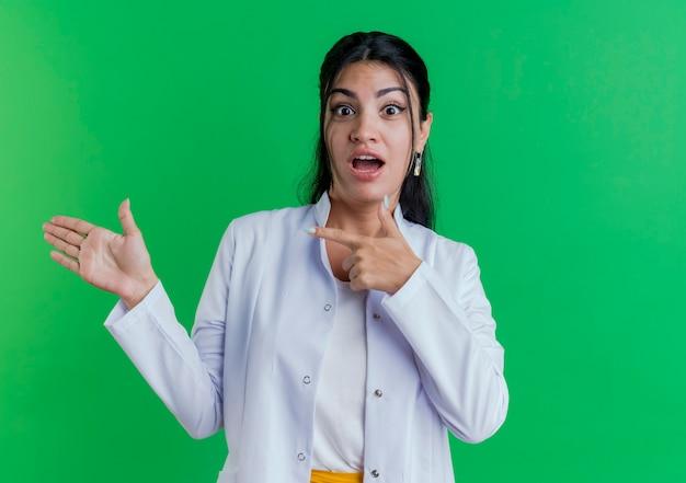 Onder de indruk jonge vrouwelijke arts die medische mantel draagt die met lege hand kijkt en ernaar wijst