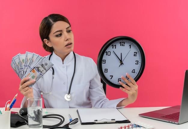 Onder de indruk jonge vrouwelijke arts die medische mantel draagt met een stethoscoop zittend aan een bureau werkt op de computer met medische hulpmiddelen die contant geld vasthoudt en kijkt naar de muurklok in de hand roze muur met kopie ruimte