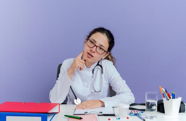 Onder de indruk jonge vrouwelijke arts die medische mantel en stethoscoop draagt ?? die aan bureau met medische hulpmiddelen zit die kant wat betreft geïsoleerd gezicht bekijkt