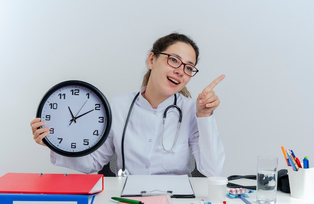Onder de indruk jonge vrouwelijke arts die medische mantel en stethoscoop en bril draagt die aan bureau met medische hulpmiddelen zit die klok kijkt en naar geïsoleerde kant wijst
