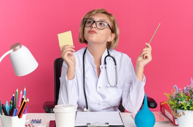Onder de indruk jonge vrouwelijke arts die medische mantel met stethoscoop en bril draagt, zit aan bureau met medische hulpmiddelen met notitiepapier met potlood geïsoleerd op roze muur