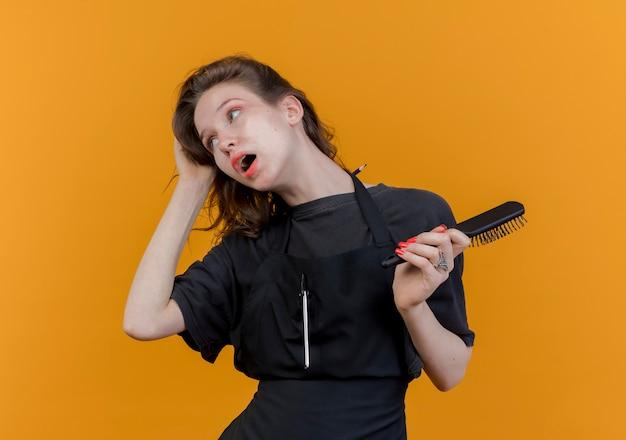 Onder de indruk jonge vrouwelijke kapper dragen uniform kijken naar kant houden kam en grijpen haar