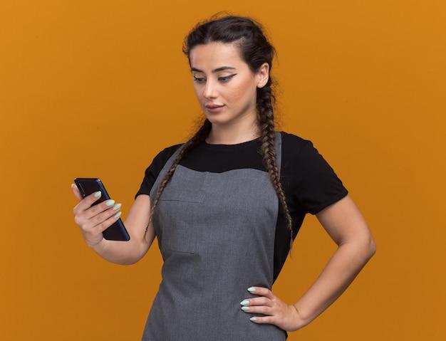 Onder de indruk jonge vrouwelijke kapper in uniform houden en kijken naar telefoon hand op heup geïsoleerd op oranje muur te zetten