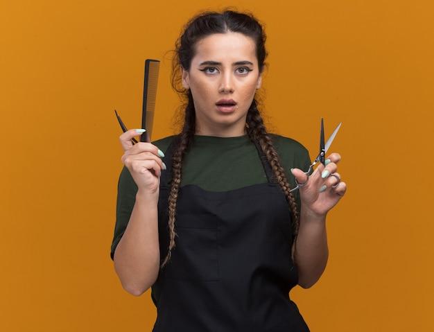 Onder de indruk jonge vrouwelijke kapper in uniform kapper tools houden geïsoleerd op oranje muur met kopie ruimte