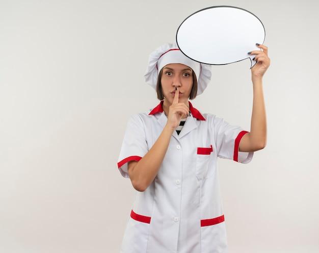 Onder de indruk jonge vrouwelijke kok in chef-kok uniforme bedrijf praatjebel en gebaren stilte geïsoleerd op wit met kopie ruimte
