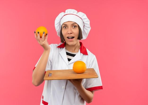 Onder de indruk jonge vrouwelijke kok in chef-kok uniforme houden van sinaasappel en snijplank met sinaasappel erop geïsoleerd op roze met kopie ruimte