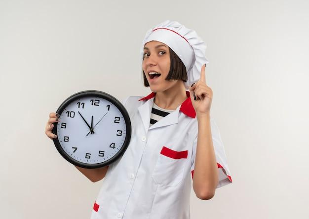 Onder de indruk jonge vrouwelijke kok in de klok van de chef-kok de eenvormige holding en het opheffen van vinger die op wit met exemplaarruimte wordt geïsoleerd