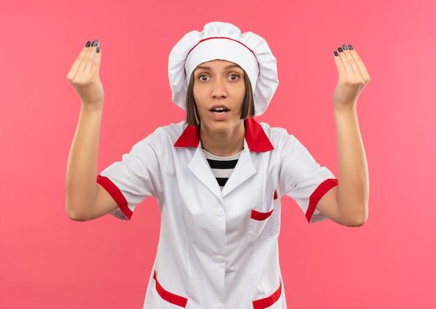 Onder de indruk jonge vrouwelijke kok in eenvormige chef-kok die uiteindegebaar doet dat op roze wordt geïsoleerd