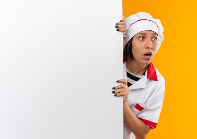 Onder de indruk jonge vrouwelijke kok in eenvormige chef-kok die zich achter bevindt en witte muur houdt en kant bekijkt die op sinaasappel met exemplaarruimte wordt geïsoleerd