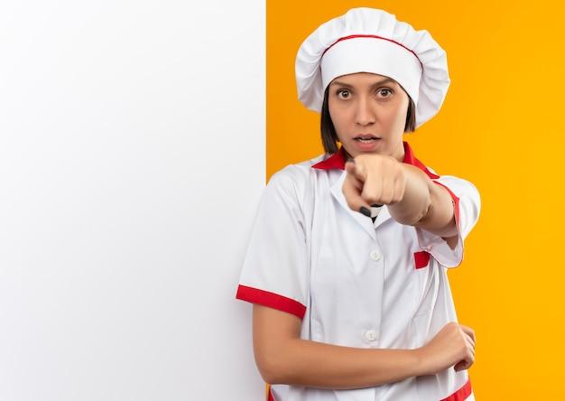 Onder de indruk jonge vrouwelijke kok in eenvormige chef-kok die zich voor witte muur bevindt en geïsoleerd op oranje met exemplaarruimte richt