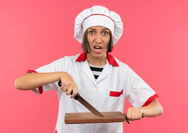 Onder de indruk jonge vrouwelijke kok in eenvormige chef-kok wat betreft snijplank met mes geïsoleerd op roze