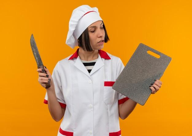 Onder de indruk jonge vrouwelijke kok in het eenvormige mes en de snijplank van de chef-kok eenvormige en bekijkt raad die op oranje wordt geïsoleerd