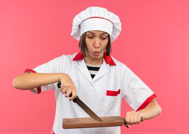 Onder de indruk jonge vrouwelijke kok in uniform chef aanraken snijplank met mes en kijken naar het geïsoleerd op roze