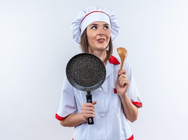 Onder de indruk jonge vrouwelijke kok in uniform van de chef-kok met koekenpan met lepel geïsoleerd op een witte achtergrond