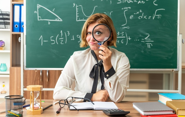 Onder de indruk jonge vrouwelijke leraar zit aan tafel met schoolhulpmiddelen met vergrootglas in de klas